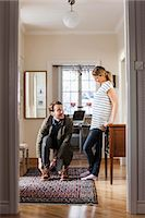 Man wearing shoes while looking at woman in house Stock Photo - Premium Royalty-Freenull, Code: 698-07588623