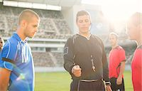 Referee tossing coin during soccer game Stock Photo - Premium Royalty-Freenull, Code: 6113-07588869