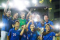 football team - Soccer team celebrating with trophy on field Stock Photo - Premium Royalty-Freenull, Code: 6113-07588877