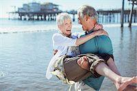 Senior man carrying wife on sunny beach Stock Photo - Premium Royalty-Freenull, Code: 6113-07589402