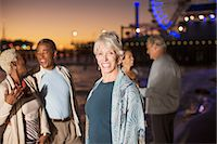 Portrait of enthusiastic senior woman with friends on beach at night Stock Photo - Premium Royalty-Freenull, Code: 6113-07589432
