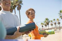 fitness   mature woman - Portrait of smiling woman with yoga mat at beach Stock Photo - Premium Royalty-Freenull, Code: 6113-07589465