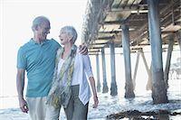 Senior couple laughing near pier at beach Stock Photo - Premium Royalty-Freenull, Code: 6113-07589478