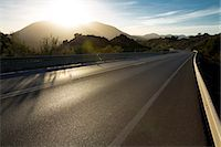 Sun shining over mountains and open road Stock Photo - Premium Royalty-Freenull, Code: 6113-07589510