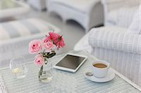 Pink roses on patio table with coffee cup and digital tablet Stock Photo - Premium Royalty-Freenull, Code: 6113-07589599