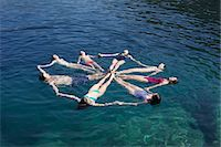 Family group of eight floating on sea in a circle Stock Photo - Premium Royalty-Freenull, Code: 649-07596123