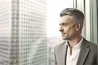 Portrait of mature businessman looking out of office window Stock Photo - Premium Royalty-Freenull, Code: 649-07596240