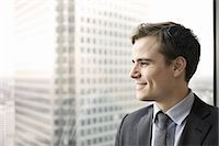 Portrait of young businessman looking out of office window Stock Photo - Premium Royalty-Freenull, Code: 649-07596241