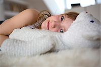 Girl lying on furry bed with teddy bear Stock Photo - Premium Royalty-Freenull, Code: 649-07596258