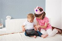 Girl watching over baby boy playing digital tablet Stock Photo - Premium Royalty-Freenull, Code: 649-07596600