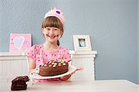 Girl showing off her birthday cake Stock Photo - Premium Royalty-Freenull, Code: 649-07596608