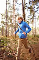 Boy running with a stick in woods Stock Photo - Premium Royalty-Freenull, Code: 649-07596725
