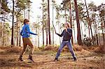 Twin brothers play fighting with sticks in forest