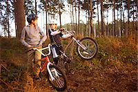 Twin brothers holding BMX bikes chatting in forest Stock Photo - Premium Royalty-Freenull, Code: 649-07596733