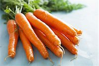Fresh carrots on a pale blue surface (close-up) Stock Photo - Premium Royalty-Freenull, Code: 659-07598392