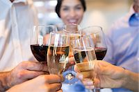 Closeup mid section of people toasting wine glasses Stock Photo - Premium Royalty-Freenull, Code: 6109-07600922