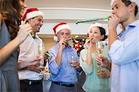 People in Santas hats with champagne flutes and noise makers Stock Photo - Premium Royalty-Freenull, Code: 6109-07600931