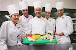 Head chef showing board of vegetables with trainees