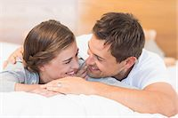 Happy couple lying on a bed Stock Photo - Premium Royalty-Freenull, Code: 6109-07601246