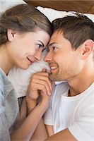 Happy couple lying on bed holding hands Stock Photo - Premium Royalty-Freenull, Code: 6109-07601273