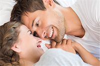 Happy couple lying on bed holding hands Stock Photo - Premium Royalty-Freenull, Code: 6109-07601274