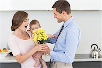 Father giving mother holding baby a bunch of yellow flowers Stock Photo - Premium Royalty-Freenull, Code: 6109-07601356