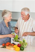 Smiling senior couple preparing a salad Stock Photo - Premium Royalty-Freenull, Code: 6109-07601376