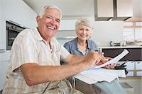 Happy couple paying their bills at the table Stock Photo - Premium Royalty-Freenull, Code: 6109-07601409