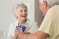 Happy senior couple playing a card game Stock Photo - Premium Royalty-Freenull, Code: 6109-07601429