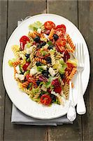 Pasta salad with olives, cherry tomatoes, iceberg lettuce and mozzarella Stock Photo - Premium Royalty-Freenull, Code: 659-07609836
