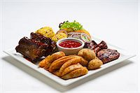 rib - Spare ribs and chicken wings with potato wedges, corn on the cob and ketchup Stock Photo - Premium Royalty-Freenull, Code: 659-07610407