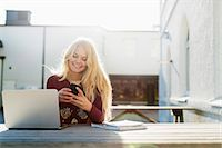 Happy teenage girl using mobile phone with laptop on table outdoors Stock Photo - Premium Royalty-Freenull, Code: 698-07611420