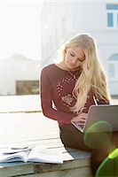 Teenage girl using laptop while looking at book on pier Stock Photo - Premium Royalty-Freenull, Code: 698-07611431