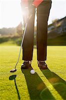 Low section of senior woman playing golf on course Stock Photo - Premium Royalty-Freenull, Code: 698-07611468