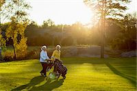 Senior women walking with golf bags on grassy area Stock Photo - Premium Royalty-Freenull, Code: 698-07611476