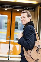 Portrait of smiling young businessman with backpack on railroad station Stock Photo - Premium Royalty-Freenull, Code: 698-07611480