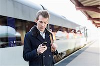 Young businessman using cell phone on railroad station Stock Photo - Premium Royalty-Freenull, Code: 698-07611481