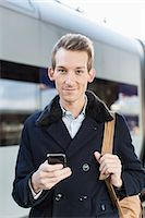 Portrait of confident young businessman holding cell phone on railroad station Stock Photo - Premium Royalty-Freenull, Code: 698-07611482