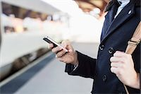 Midsection of businessman using cell phone on railroad station Stock Photo - Premium Royalty-Freenull, Code: 698-07611484