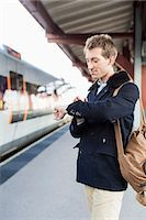 Young businessman looking at watch on railroad station Stock Photo - Premium Royalty-Freenull, Code: 698-07611485