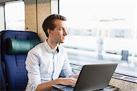 Young businessman using laptop on train Stock Photo - Premium Royalty-Freenull, Code: 698-07611486