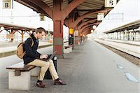 Full length side view of young businessman using laptop on railroad station Stock Photo - Premium Royalty-Freenull, Code: 698-07611492