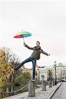 Full length of businessman with umbrella balancing on bollard outdoors Stock Photo - Premium Royalty-Freenull, Code: 698-07611495