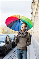 Young businessman with umbrella walking on footpath Stock Photo - Premium Royalty-Freenull, Code: 698-07611496