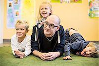 Portrait of playful children with teacher in kindergarten Stock Photo - Premium Royalty-Freenull, Code: 698-07611548