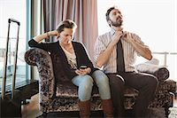 Business couple relaxing on chaise longue in hotel room Stock Photo - Premium Royalty-Freenull, Code: 698-07611588