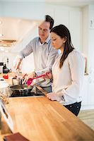 Couple cooking together in kitchen Stock Photo - Premium Royalty-Free, Artist: Blend Images, Code: 698-07611632