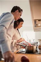 Couple preparing food in domestic kitchen Stock Photo - Premium Royalty-Freenull, Code: 698-07611634