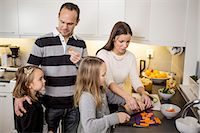 popping (bursting not corks or pimples) - Family cutting vegetables at kitchen counter Stock Photo - Premium Royalty-Freenull, Code: 698-07611730