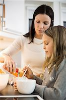 Mother and daughter adding flavor in cup at kitchen Stock Photo - Premium Royalty-Freenull, Code: 698-07611732
